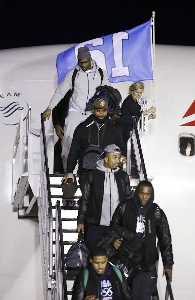 Seattle Seahawks players walk down stairs off the plane on the team's arrival Monday, Feb. 3, 2014, at Seattle-Tacoma International Airport in Seattle. The Seahawks beat the Denver Broncos 43-8 in the Super Bowl on Sunday
