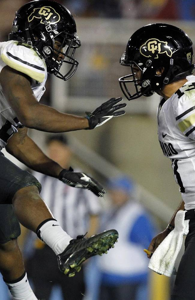 Colorado running back Tony Jones, left, celebrates his touchdown with quarterback Sefo Liufau in the second half of their NCAA college football game against UCLA, Saturday, Nov. 2, 2013, in Pasadena, Calif. UCLA won the game 45-23