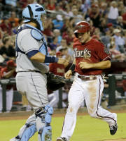 Arizona Diamondbacks' Eric Chavez scores on a Wil Nieves sacrifice fly as Tampa Bay Rays catcher Jose Molina watches during the fifth inning of a baseball game, Wednesday, Aug. 7, 2013, in Phoenix. (AP Photo/Matt York)