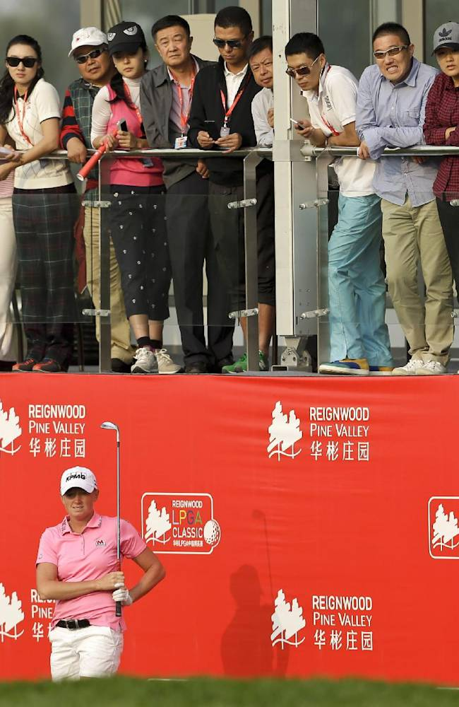 US Stacy Lewis follows a ball on the 18th hole after her ball landed very close to the red billboard during the first round of the Reignwood LPGA Classic golf tournament at Pine Valley Golf Club on the outskirts of Beijing, China, Thursday, Oct. 3, 2013