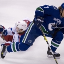 Vancouver Canucks left wing David Booth (7) fights for control of the puck with New York Rangers center Derek Stepan (21) during the first period of NHL action in Vancouver, British Columbia, Tuesday, April 1, 2014 The Associated Press