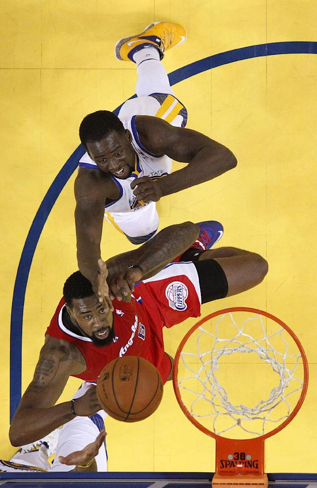 Los Angeles Clippers center DeAndre Jordan, bottom, shoots against Golden State Warriors small forward Draymond Green during the first half of Game 6 of an opening-round NBA basketball playoff series in Oakland, Calif., Thursday, May 1, 2014