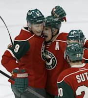 Minnesota Wild left wing Zach Parise, center, celebrates with teammates Mikko Koivu (9), of Finland, and Ryan Suter (20) after scoring a goal against Vancouver Canucks during the first period of an NHL hockey game in St. Paul, Minn., Tuesday, Dec. 17, 2013. (AP Photo/Ann Heisenfelt)