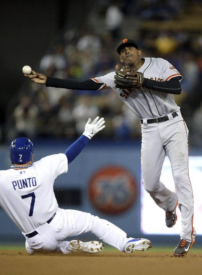 San Francisco Giants shortstop Joaquin Arias, right, throws to first base after forcing out Los Angeles Dodgers' Nick Punto during the third inning of a baseball game on Friday, Sept. 13, 2013, in Los Angeles