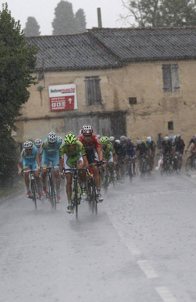 the pack rides in the rain during the nineteenth stage of the Tour de France cycling race over 208.5 kilometers (129.6 miles) with start in Maubourguet and finish in Bergerac, France, Friday, July 25, 2014