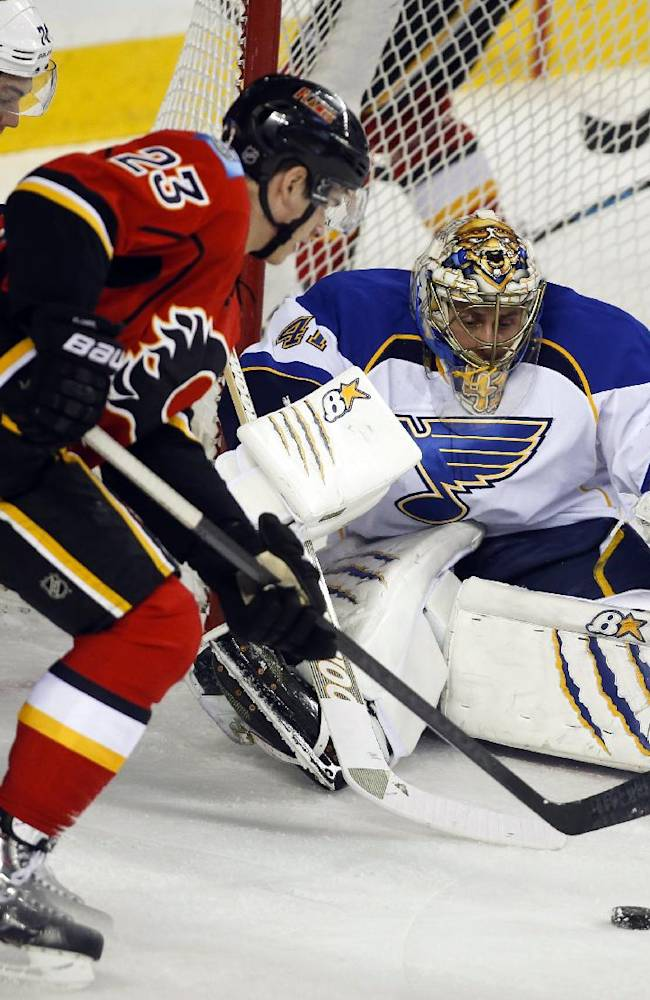 St. Louis Blues' goalie Jaroslav Halak, third from left, from Slovakia, sprawls on the ice as Calgary Flames' Sean Monahan (23) tries to score during first-period NHL hockey game action in Calgary, Alberta, Monday, Dec. 23, 2013