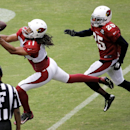 Arizona Cardinals wide receiver Larry Fitzgerald (11) pulls in a pass as teammate Jerraud Powers defends during an NFL football training camp, Monday, Aug. 11, 2014, in Glendale, Ariz The Associated Press