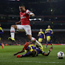 Arsenal's Alex Oxlade-Chamberlain, top, competes for the ball with Swansea City's Ashley Williams during the English Premier League soccer match between Arsenal and Swansea City at the Emirates Stadium in London, Tuesday, March 25, 2014