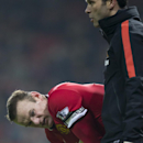 In this Nov. 29, 2014 photo, Manchester United's Wayne Rooney waits by the side of the pitch after being injured during the English Premier League soccer match between Manchester United and Hull City at Old Trafford Stadium, Manchester, England. The Manc