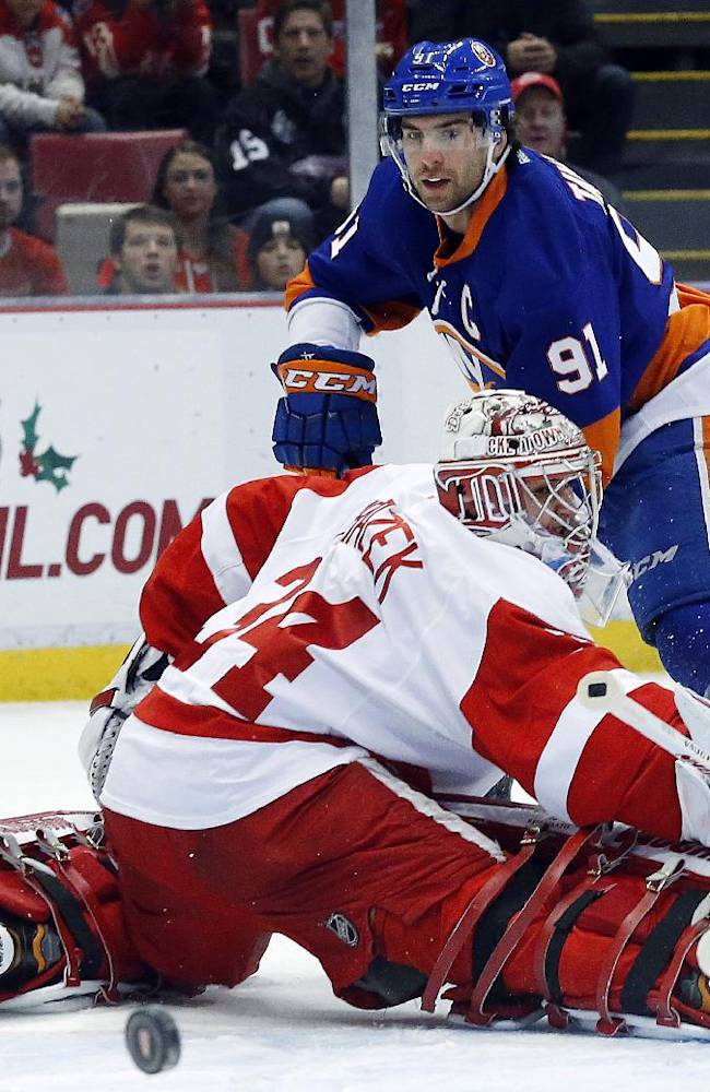 New York Islanders center John Tavares (91) shoots on Detroit Red Wings goalie Petr Mrazek (34), of the Czech Republic, in the first period of an NHL hockey game, Monday, Dec. 23, 2013, in Detroit
