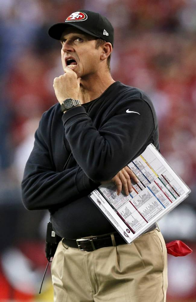 San Francisco 49ers head coach Jim Harbaugh looks at the scoreboard against the Arizona Cardinals during the second half of an NFL football game, Sunday, Dec. 29, 2013, in Glendale, Ariz. The 49ers won 23-20