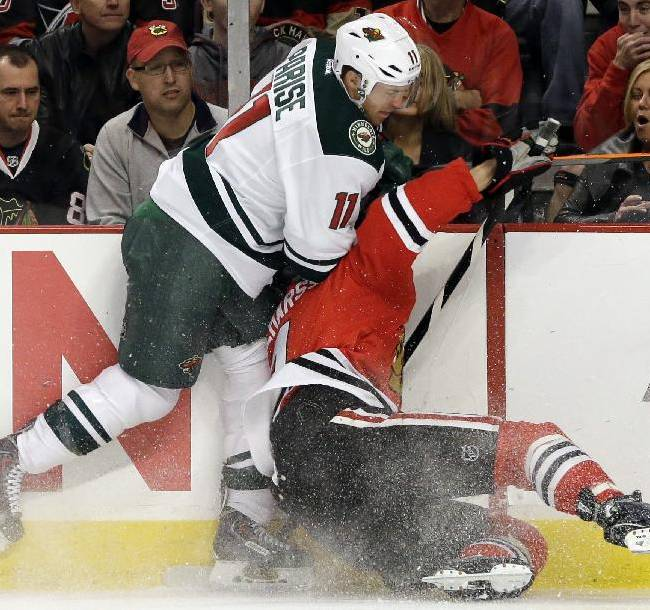 Chicago Blackhawks' Niklas Hjalmarsson (4), right, is checked by Minnesota Wild's Zach Parise (11) during the first period of an NHL hockey game in Chicago, Saturday, Oct. 26, 2013