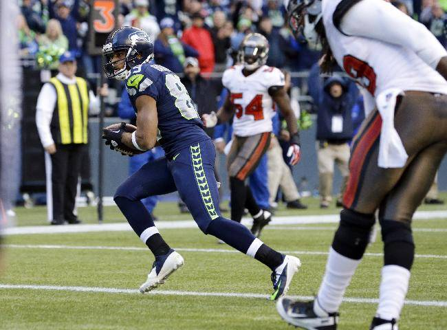 Seattle Seahawks' Doug Baldwin, left, scores a touchdown on a reception in the second half of an NFL football game against the Tampa Bay Buccaneers, Sunday, Nov. 3, 2013, in Seattle