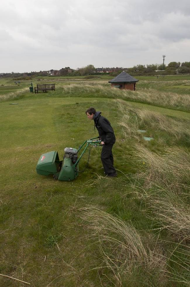 A greenkeeper mows the 13th hole at Royal Liverpool Golf Club before the British Open golf championships, Hoylake, England, Wednesday, April 23, 2014. The 2014 Open Championship which will be played at Royal Liverpool from July 17-20, 2014