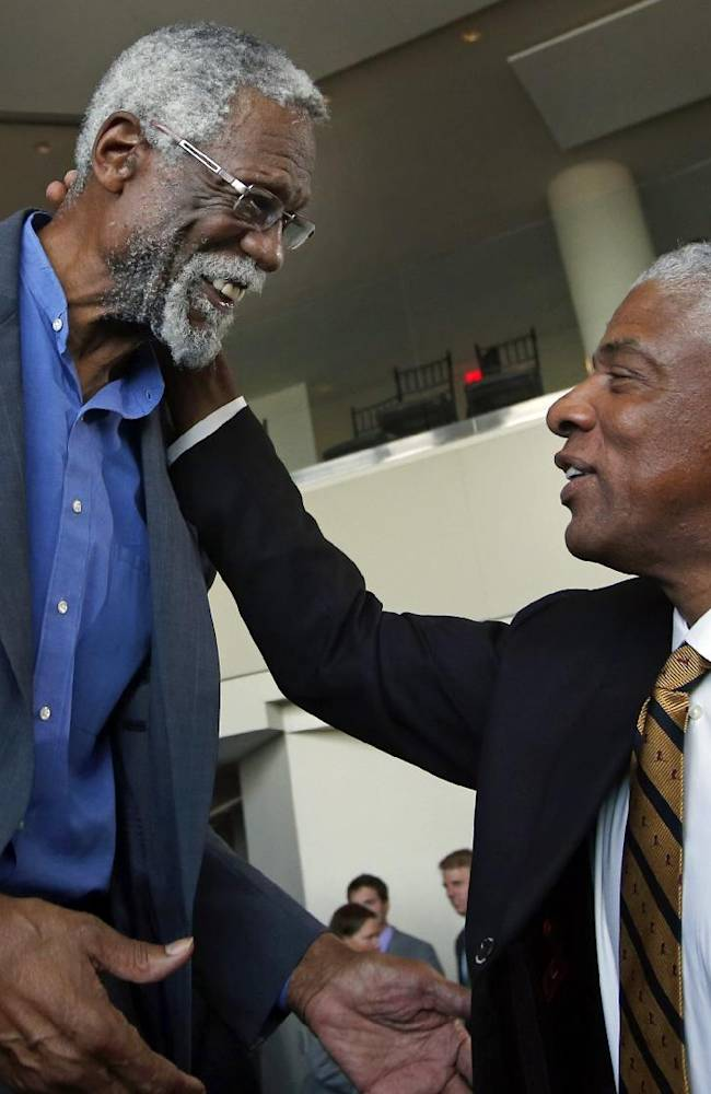 Julius Erving, right, former Philadelphia 76ers basketball great, greets former Boston Celtics basketball star Bill Russell after a statue honoring Russell was unveiled at City Hall Plaza in Boston, Friday, Nov. 1, 2013