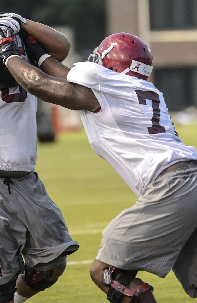 Alabama offensive lineman Arie Kouandjio (77) works through drills with offensive lineman Isaac Luatua (68) as offensive line coach Mario Cristobal watches, left, during football practice, Wednesday, Aug. 6, 2014, in Tuscaloosa, Ala
