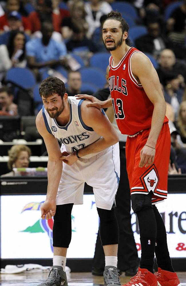 Minnesota Timberwolves forward Kevin Love, left, rubs his right elbow as he is guarded by Chicago Bulls center Joakim Noah during the first quarter of an NBA basketball game in Minneapolis, Wednesday, April 9, 2014. Love said he hyperextended his right elbow in the first half. The Bulls won 102-87
