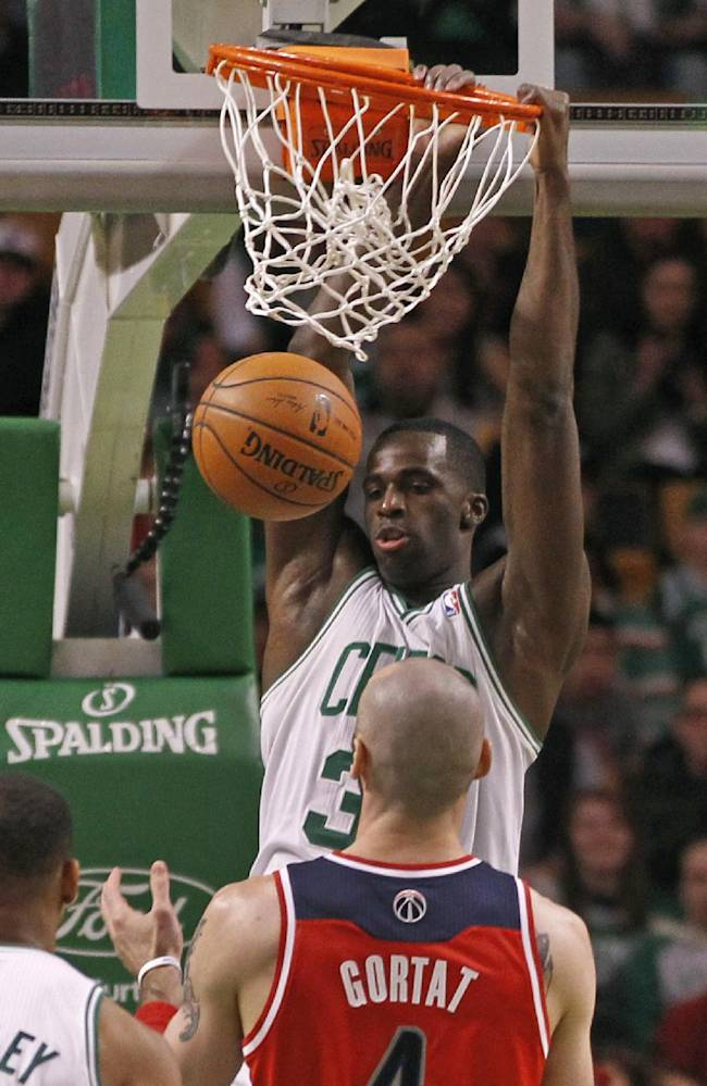 Boston Celtics forward Brandon Bass, top, dunks against Washington Wizards center Marcin Gortat (4) during the first quarter of an NBA basketball game in Boston, Wednesday, April 16, 2014