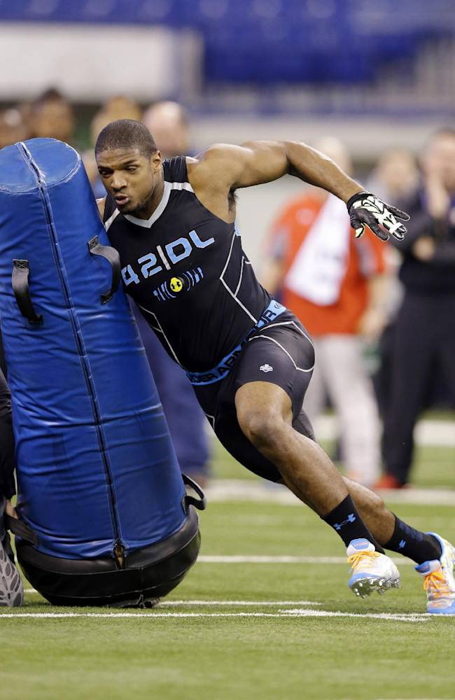 Missouri defensive lineman Michael Sam runs a drill at the NFL football scouting combine in Indianapolis, Monday, Feb. 24, 2014