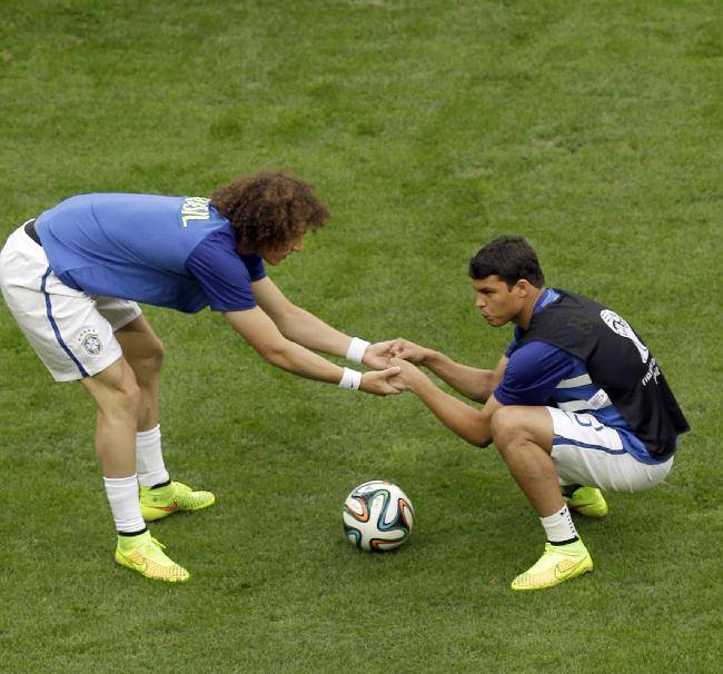 Brazil's Thiago Silva, right, and David Luiz stretch during warm-up before the World Cup third-place soccer match between Brazil and the Netherlands at the Estadio Nacional in Brasilia, Brazil, Saturday, July 12, 2014