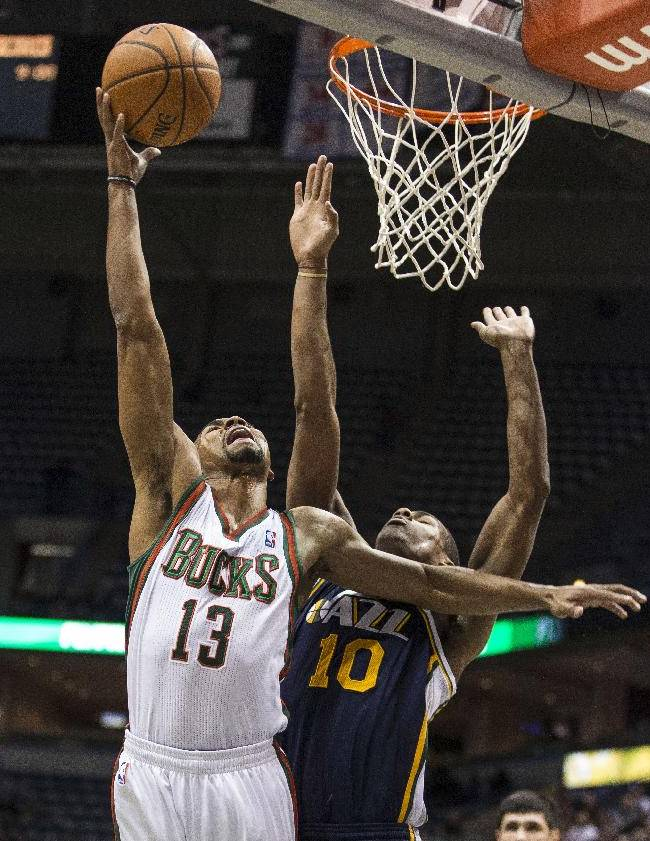 Milwaukee Bucks' Ramon Sessions, left, shoots over Utah Jazz Alec Burks during the first half of an NBA basketball game Monday, March 3, 2014, in Milwaukee