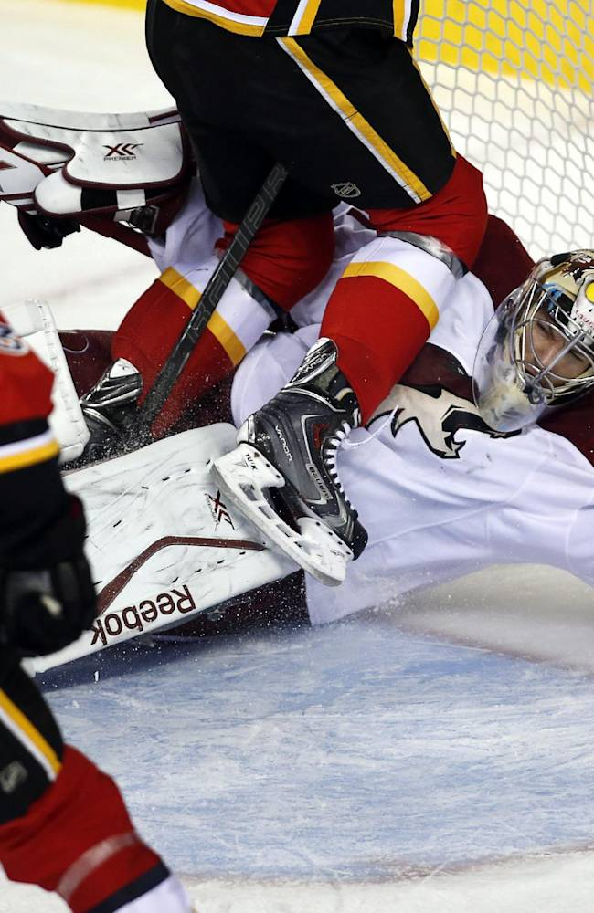 Phoenix Coyotes goalie Mike Smith, right, is shoved into the net as Calgary Flames' Ben Street (38) tries to score during first-period NHL preseason hockey game action in Calgary, Alberta, Wednesday, Sept. 25, 2013