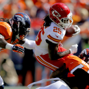 Kansas City Chiefs running back Jamaal Charles (25) is tripped up by Denver Broncos strong safety T.J. Ward (43) and Quinton Carter during the first half of an NFL football game, Sunday, Sept. 14, 2014, in Denver. (AP Photo/Jack Dempsey)