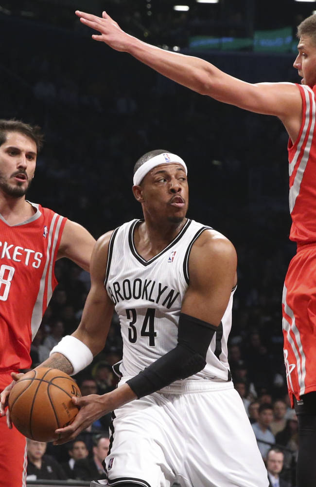 Brooklyn Nets forward Paul Pierce (34) looks to pass against Houston Rockets forward Omri Casspi (18) and forward Chandler Parsons (25) during the first half of their NBA basketball game at the Barclays Center, Tuesday, April 1, 2014, in New York