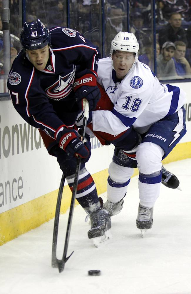 Columbus Blue Jackets' Dalton Prout, left, works for the puck against Tampa Bay Lightning's Ondrej Palat, of the Czech Republic, in the first period of an NHL hockey game in Columbus, Ohio, Tuesday, Dec. 3, 2013