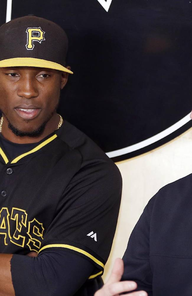 Pittsburgh Pirates left fielder Starling Marte sits with General Manager Neal Huntington, right, during a news conference where his contract extension was discussed before a spring exhibition baseball game against the New York Yankees in Bradenton, Fla., Thursday, March 27, 2014
