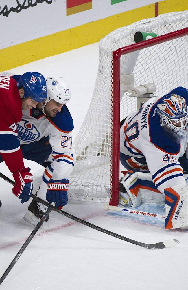 Edmonton Oilers' goaltender Devan Dubnyk, right, makes a save against Montreal Canadiens' Mike Blunden, left, as Oilers' Boyd Gordon defends during the first period of an NHL hockey game in Montreal, Tuesday, Oct. 22, 2013