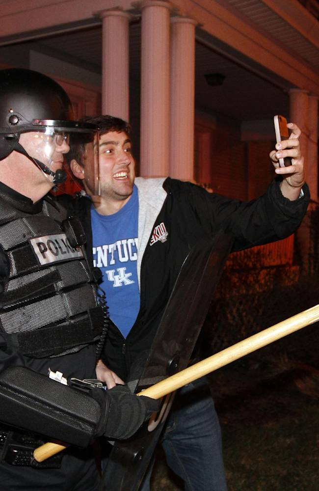 Eastern Kentucky University junior Eric Kuertz, right, takes a selfie with UK Police officer Lt. Greg Hall as Kentucky fans react to their teams semi-final victory on State St., near the University of Kentucky campus, Saturday, April 5, 2014, in Lexington, Ky. The win advances the Wildcats to the championship game of the NCAA men's college basketball tournament