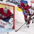 Montreal Canadiens goaltender Carey Price, left, keeps an eye on the play as Canadiens' David Desharnais, center, defends against Colorado Avalanche player Matt Duchene (9) during the first period of an NHL hockey game, Saturday, Oct. 18, 2014 in Montrea