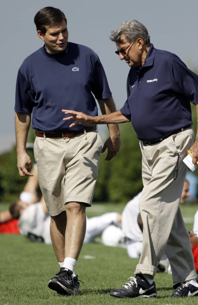 This Aug. 8, 2008 file photo shows Penn State football coach Joe Paterno, right, walking with his son and quarterback coach Jay Paterno as players stretch out during practice in State College, Pa. Jay Paterno is the author of the book,