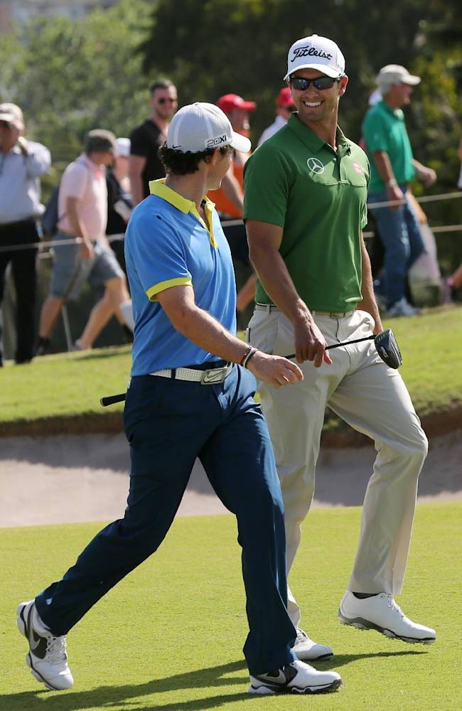Rory McIlroy, left, of Northern Ireland walks with Australia's Adam Scott during their third round at the Australian Open Golf tournament in Sydney, Australia, Saturday, Nov. 30, 2013