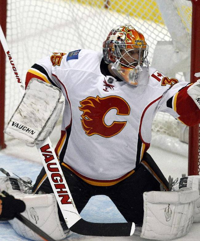 Calgary Flames goalie Joey MacDonald (35) keeps his glove on the puck on a shot by Anaheim Ducks right wing Corey Perry (10) during the third period of an NHL hockey game, Wednesday, Oct. 16, 2013, in Anaheim, Calif. Ducks won the game 3-2