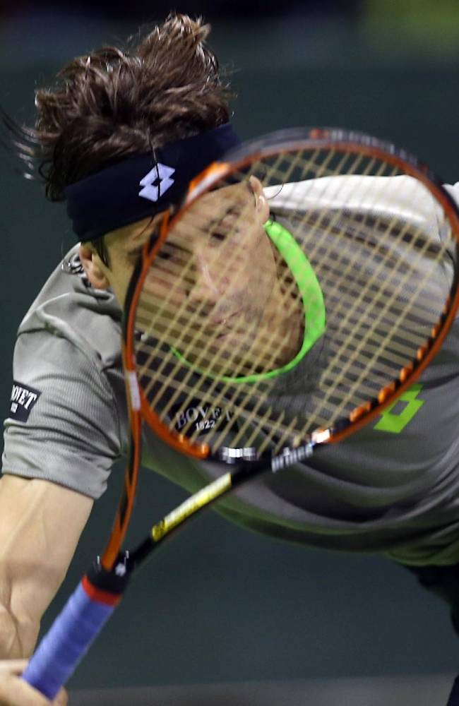 David Ferrer of Spain returns the ball to Daniel Brands of Germany during the Qatar ATP Open Tennis tournament in Doha, Qatar, Wednesday, Jan. 1, 2014