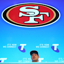 Jarryd Hayne, center, announces his free agent contract with the National Football League team the San Francisco 49ers at a press conference in Sydney, Tuesday, March 3, 2015. Australian rugby star Hayne has agreed to a contract with the San Francisco 49ers, a person with knowledge of the deal said Tuesday. (AP Photo/Rick Rycroft)