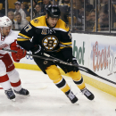 Boston Bruins' Milan Lucic (17) keeps the puck from Detroit Red Wings' Niklas Kronwall during the second period of Game 1 of a first-round NHL playoff hockey series in Boston on Friday, April 18, 2014 The Associated Press