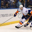 New York Islanders' John Taveras (91) reaches for the puck in front of St. Louis Blues' T.J. Oshie (74) during the first period of an NHL hockey game, Thursday, Dec. 11, 2014, in St. Louis The Associated Press