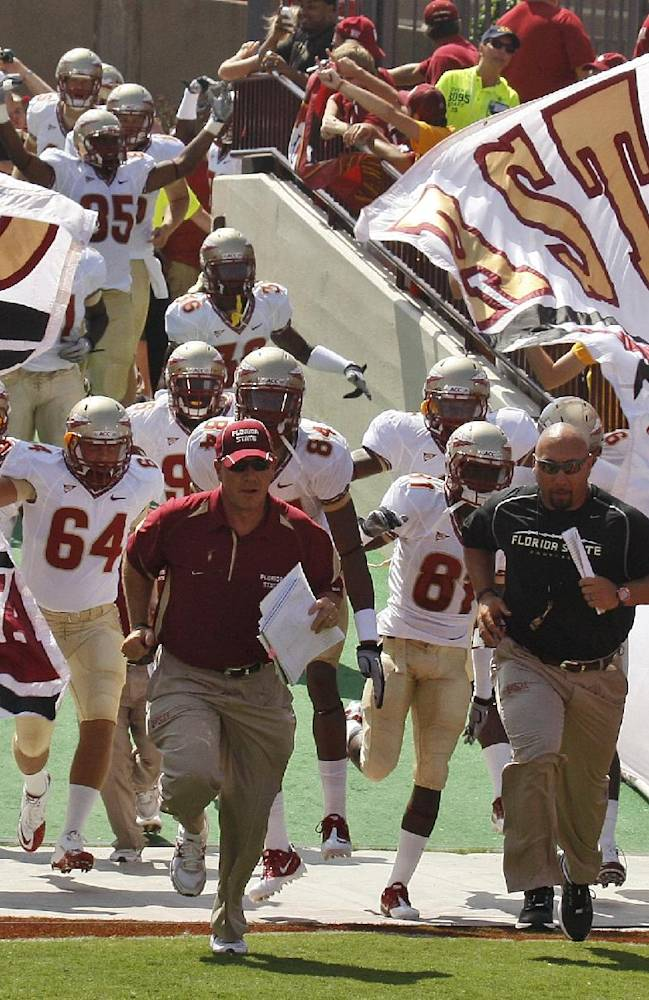 In this Sept. 11, 2010, file photo, Florida State players and coaches run onto the field before an NCAA college football game against Oklahoma in Norman, Okla. A new era in college football is here. After years of deriding the BCS, fans will finally get what they wanted with the new College Football Playoff. The top-ranked Seminoles open the season on Saturday against Oklahoma State in Arlington, Texas