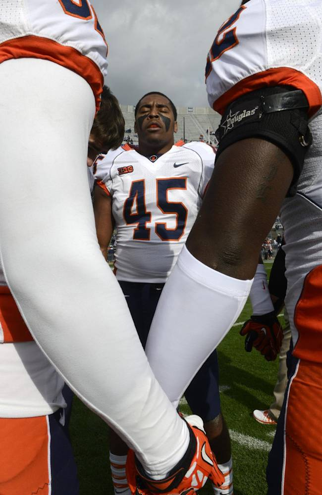Illinois linebacker Jonathan Brown prays with teammates before an NCAA college football game against Penn State in State College, Pa., Saturday, Nov. 2, 2013
