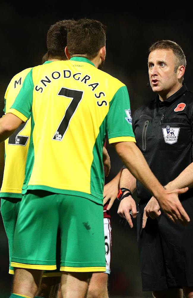 Norwich City's Robert Snodgrass confronts referee Jon Moss (right) during the English Premier League match at Carrow Road, Norwich, England, Saturday, Nov. 9, 2013