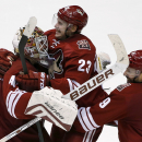 Arizona Coyotes' Oliver Ekman-Larsson (23), of Sweden, celebrates his game-winning goal against the Edmonton Oilers with teammates Sam Gagner (9) and Devan Dubnyk, left, during overtime of an NHL hockey game Tuesday, Dec. 16, 2014, in Glendale, Ariz. The