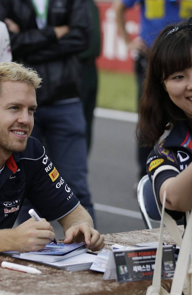Red Bull driver Sebastian Vettel of Germany poses for a photo with a fan during a autograph signing session at the Korean Formula One Grand Prix at the Korean International Circuit in Yeongam, South Korea, Saturday, Oct. 5, 2013