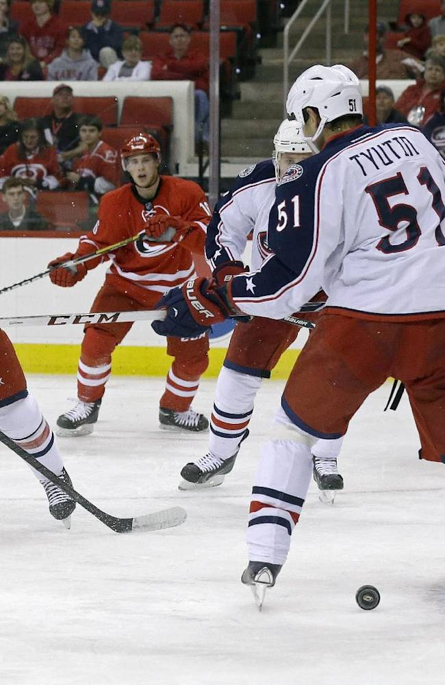 Carolina Hurricanes' Nathan Gerbe (14) is pressured by Columbus Blue Jackets' Andrew Joudrey as Blue Jackets' Fedor Tyutin (51), of Russia, and goalie Mike McKenna (30) defend the goal during the second period of an NHL preseason hockey game in Raleigh, N.C., Wednesday, Sept. 18, 2013