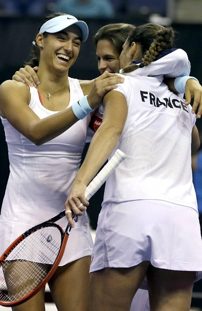 France's Caroline Garcia, left, celebrates with Virginie Razzano, right, and team captain Amelie Mauresmo after France defeated the United States in Fed Cup world group playoff tennis Sunday, April 20, 2014, in St. Louis. France won three of five matches allowing them to advance to the elite World Group in 2015