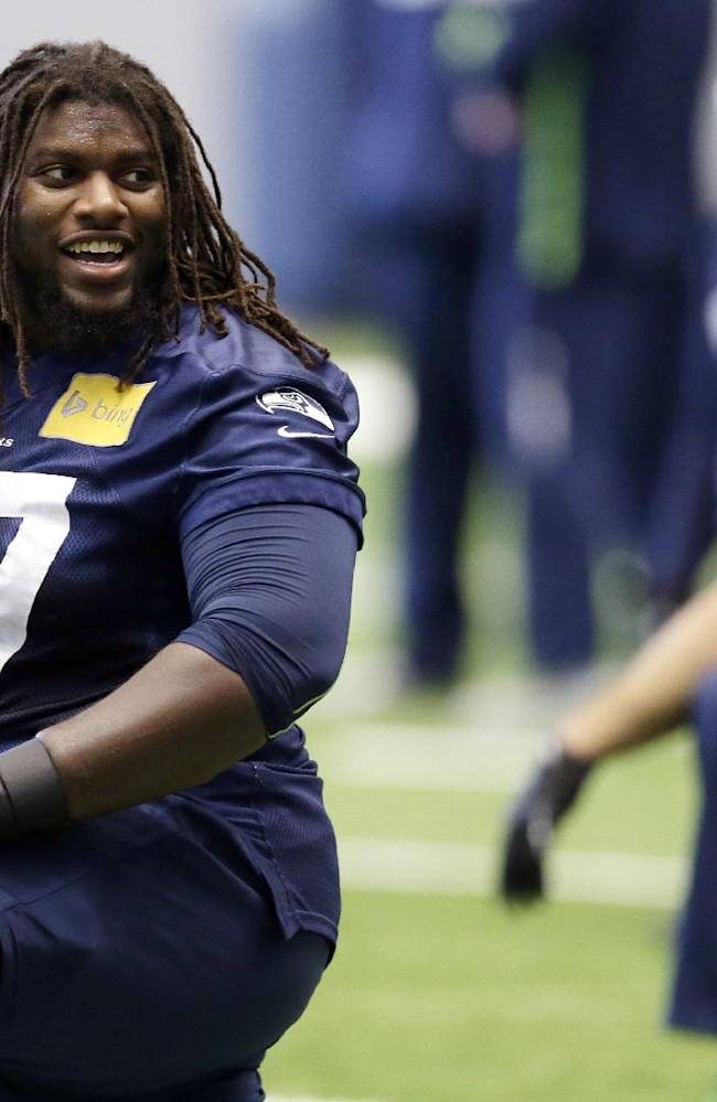 Seattle Seahawks guard James Carpenter, left, stretches during warm-ups before NFL football practice at the team's indoor facility Friday, Jan. 17, 2014, in Renton, Wash. The Seahawks host the San Francisco 49ers in the NFC championship on Sunday