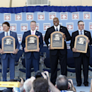 National Baseball Hall of Fame inductees, from left, Bobby Cox, Tony La Russa, Tom Glavine, Frank Thomas, Greg Maddux and Joe Torre hold their plaques after an induction ceremony at the Clark Sports Center on Sunday, July 27, 2014, in Cooperstown, N.Y. (AP Photo/Mike Groll)