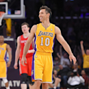 Los Angeles Lakers' Steve Nash, center, smiles after picking up an assist to take sole possession of third place for NBA all-time assists, during the first half of an NBA basketball game against the Houston Rockets, Tuesday, April 8, 2014, in Los Angeles